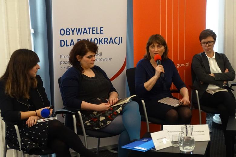 zdjęcie: na krzesłach siedzą cztery kobiety, jedna z nich mówi do mikrofonu