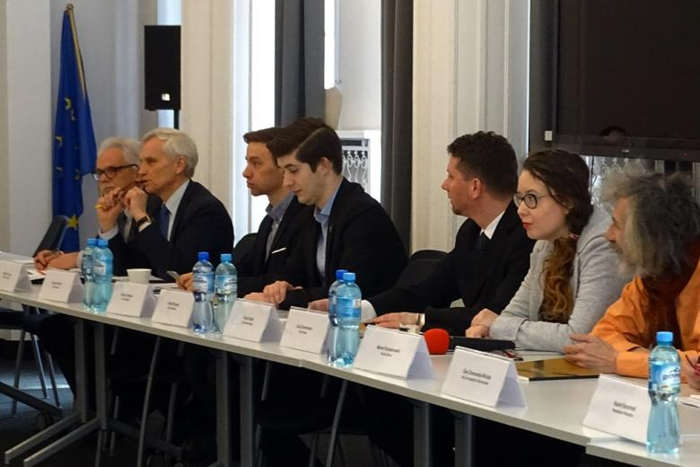 zdjęcie: przy białych stołach siedzi kilka osób, w roku sali widać flagę Unii Europejskiej