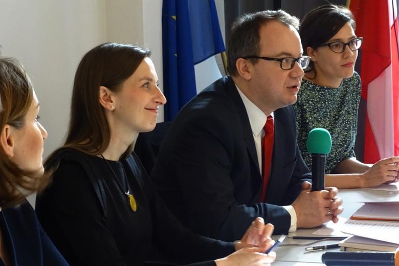 zdjęcie: z profilu widać trzy kobiety i mężczyznę w garniturze, który mówi do mikrofonu