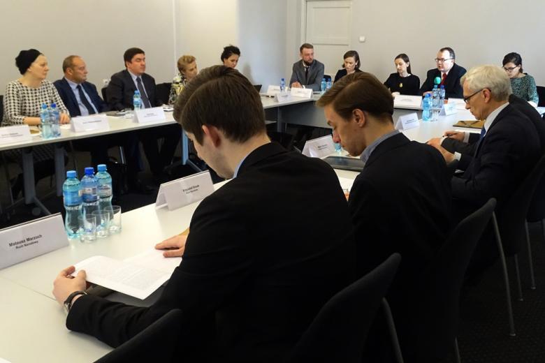 zdjęcie: przy stołach siedzących na przeciw siebie siedzi kilkanaście osób