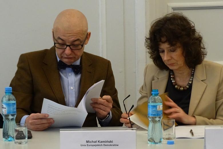 zdjęcie: mężczyzna w jasnej marynarce i muszce ogląda raport, obok niego siedzi kobieta w jasnnym żakiecie