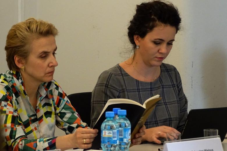 zdjęcie: kobieta w krótkich blond włosach i kolorowej bluzce we wzory przegląda raport, obok niej siedzi kobieta w ciemnych włosach i szarej sukience