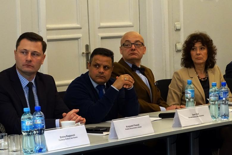 zdjęcie: przy stole siedzi trzech mężczyzn i jedna kobieta