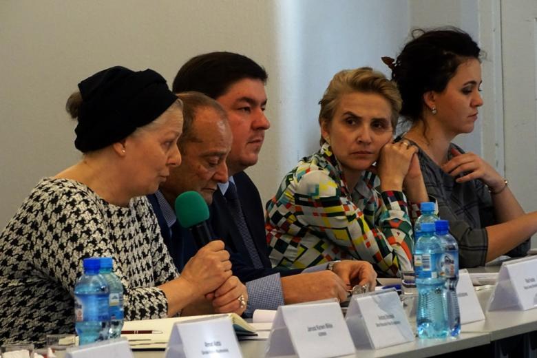 zdjęcie: przy stole siedzi dwóch mężczyzn i trzy kobieta, jedna z nich mówi do mikrofonu