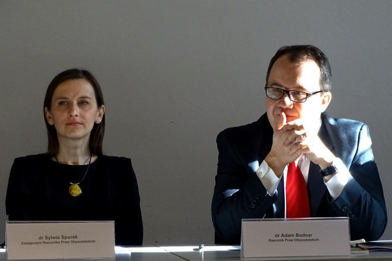 zdjęcie: po lewej stronie siedzi kobieta w czarnej sukience obok niej mężczyzna w garniturze