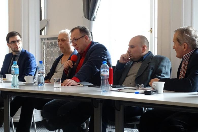 zdjęcie; przy stole siedzi pięciu mężczyzn jeden z nich mówi do mikrofonu