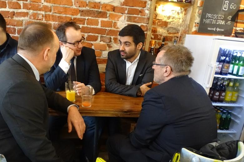 zdjęcie: przy małym stoliku w kawiarni siedzi czterech mężczyzn w garniturach