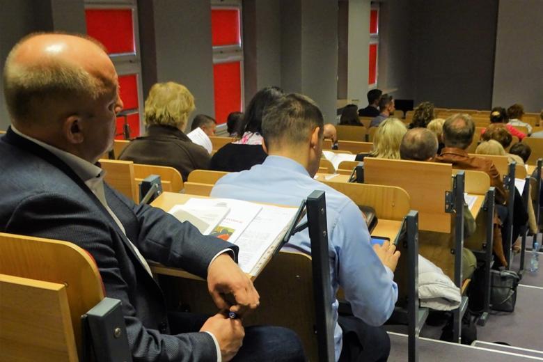 zdjęcie: kilka osób siedzi na sali, na stolikach przed nimi są materiały na temat RPO