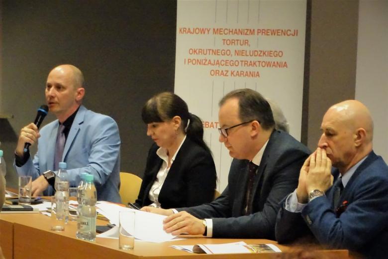 zdjęcie:za stołem prezydialnym siedzi kilka osób