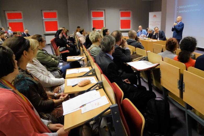 zdjęcie: mężczyzna swoi i mówi do do mikrofonu, przed nimi siedzi kilkanaście osób