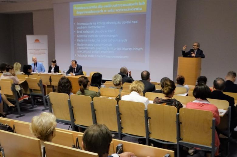 zdjęcie: kilkanaście osób siedzi na sali, przed nimi przy mównicy stoi mężczyzna