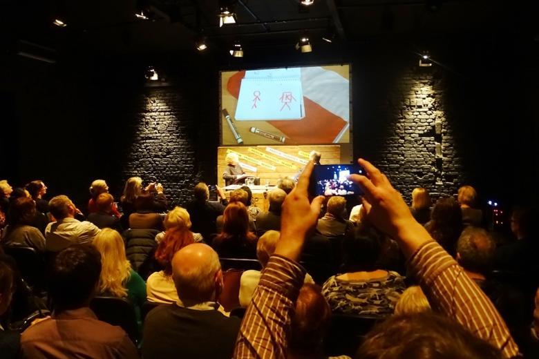 zdjęcie: na pierwszym planie widać uniesione w górę ręce trzymające telefon komórkowy - uczestnik spotkania robi zdjęcie osobom siedzącym na scenie