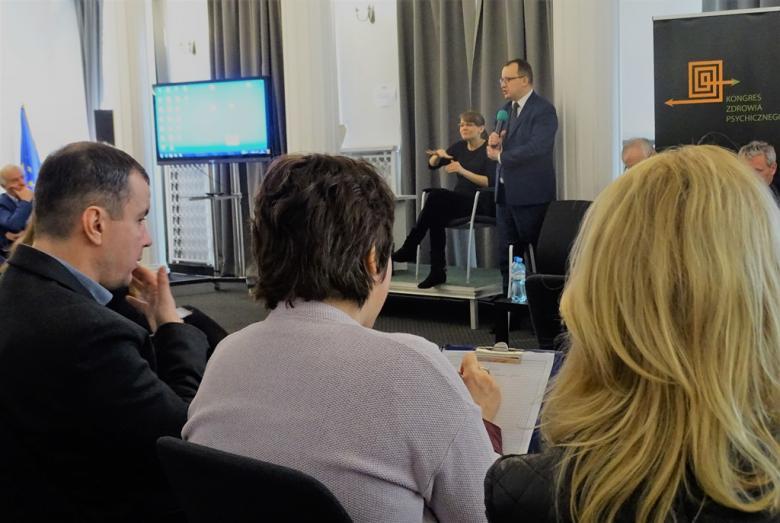zdjęcie: na pierwszym planie tyłem siedzą trzy osoby, jedna z nich notuje, przed nimi stoi mężczyzna mówiący do mikrofonu