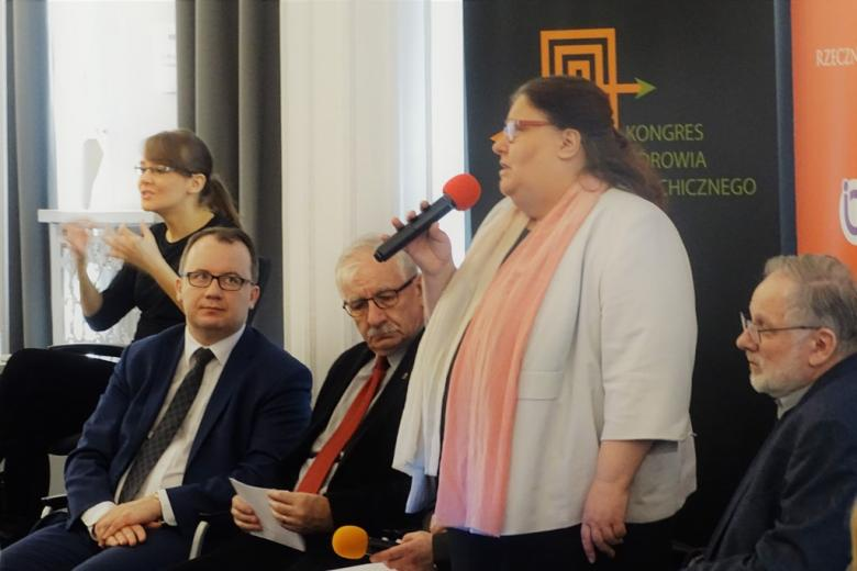 zdjęcie: kilka osób siedzi na krzechałach, po środku stoi kobieta, która mówi do mikrofonu