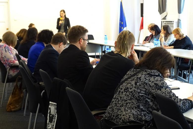 zdjęcie: przy białych stołach ustawionych naprzeciw siebie siedzi kilka osón, u szczytu stołu stoi kobieta w sukience