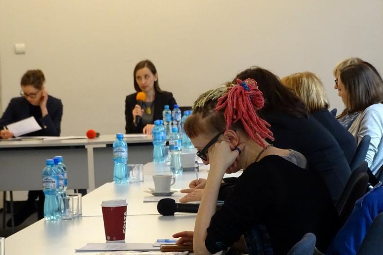 zdjęcie: po prawej stronie widać siedzące bokiem kobiety, na wprost stoi kobieta w sukience, która mówi do mikrofonu