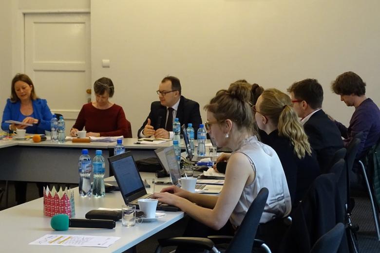 zdjęcie: kilka osób siedzi przy białych stołach, mężczyzna w garniturze mówi do mikrofonu