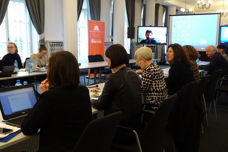 zdjęcie: kilka osób siedzi przy stołach, w tle widać telewizor z połączeniem wideokonferencji