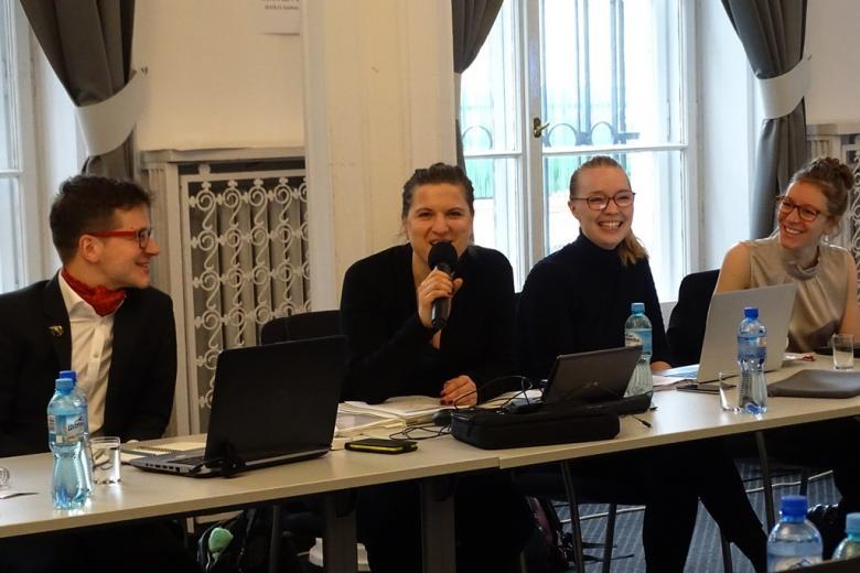 zdjęcie: przy stole siedzą cztery osoby, mężczyzna mówi do mikrofonu