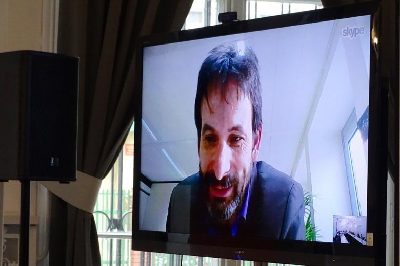 zdjęcie: telewizor, na którym wyświetla się wideokonferencja z mężczyzną