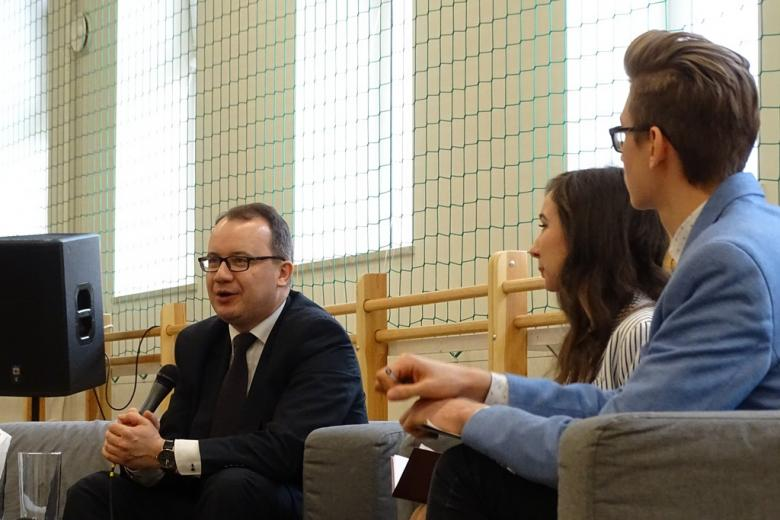 zdjęcie: od lewej strony na kanapie siedzi mężczyzna, obok dziewczyna i młody chłopak w okularach