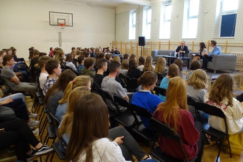 zdjęcieL na sali gimnastycznej siedzi kilkadziesiąt osób, w tle widać dwie kanapy, na których siedzi mężczyzna i dwoje młodych ludzi