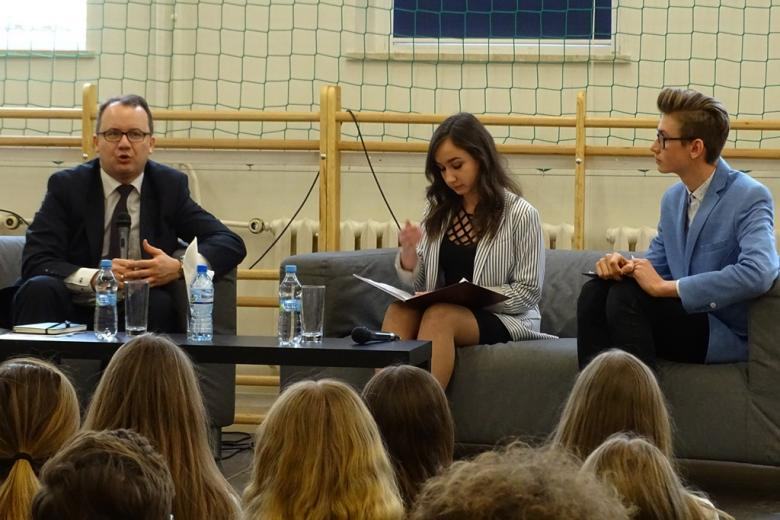 zdjęcie: w oddali widać siedzącego na szarej kanapie mężczyznę w garniturze, który mówi do mikrofonu, na kanapie obok siedzi chłopak i dziewczyna