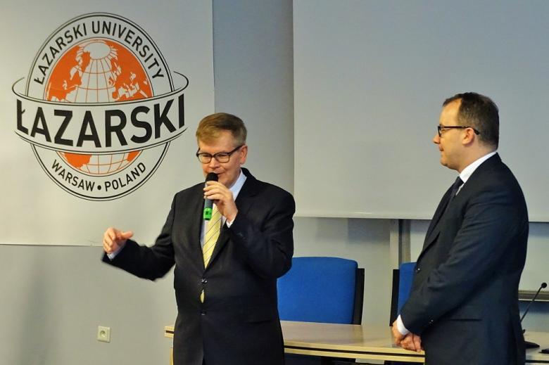zdjęcie: na aubli wykładowej stoi dwóch mężczyzn w garniturach