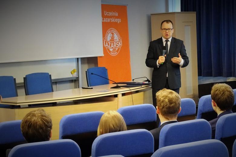 zdjęcie: mężczyzna w garniturze stoi na auli wykładowej, przed nim siedzi kilka osób