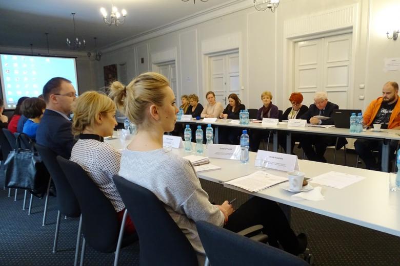 zdjęcie: przy białych stołach ustawionych naprzeciwsiebie siedzi kilkanaście osób