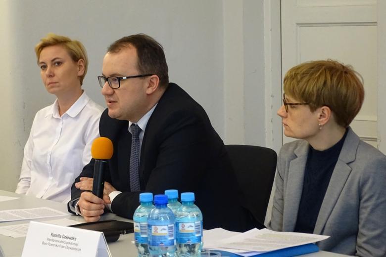 zdjęcie: przy białym stole siedzą dwie kobiety, pomiędzy nimi mężczyzna w garniturze, który mówi do mikrofonu