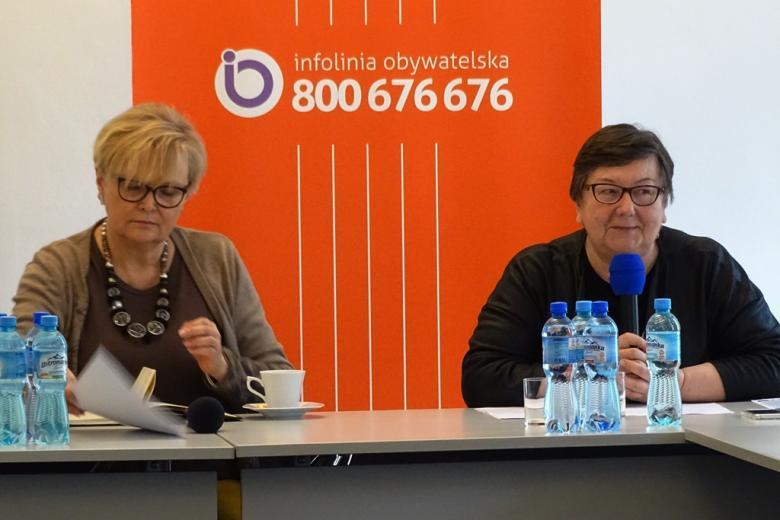 zdjęcie: przy białam stole siedzą dwie kobiety w okularach, blodynka po lewej stronie przegląda notatki, po prawej stronie - kobieta w ciemnych krótkich włosach mówi do mikrofonu