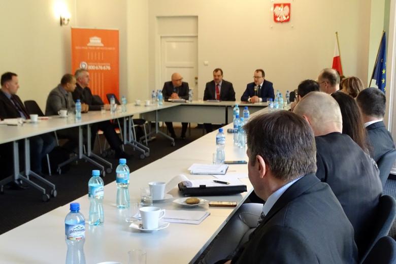 zdjęcie: kilkanaście osób siedzi przy białych stołach ustawionych w prostokąt, na pierwszym planie widać mężczyn w ciemnych garniturach, w tle za stołami widać pomarańczowy baner