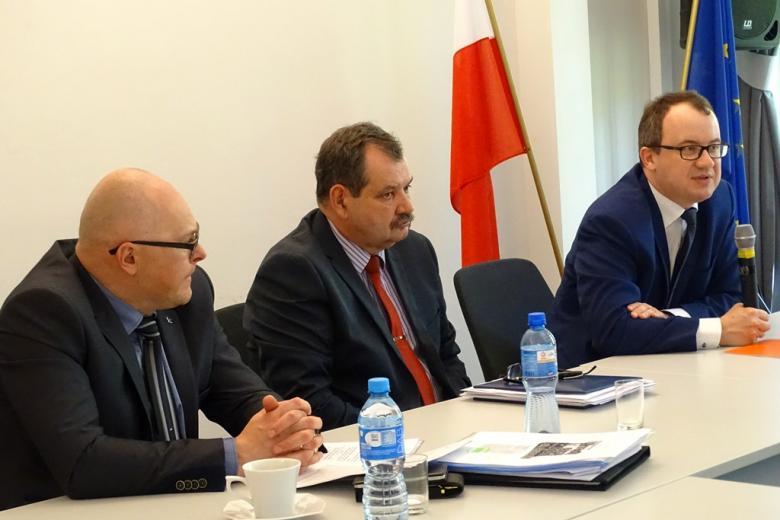 zdjęcie: trzej mężczyźni siedzą przy stole konferencyjnym, za mężczyzną po prawej stronie widać flegi Polski i Unii Europejskiej