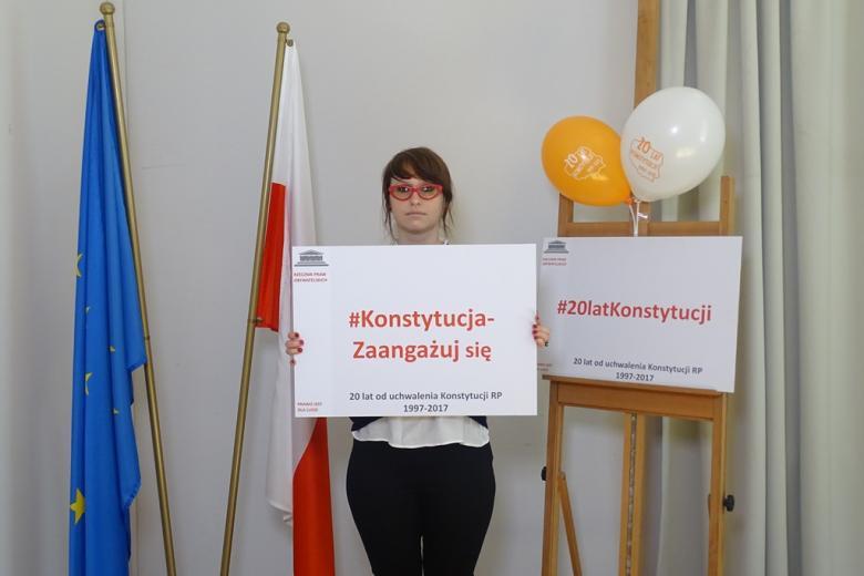 zdjęcie: kobieta w czerwonych okularach tryma tablicę z napisem Konstytucja- zaangażuj się