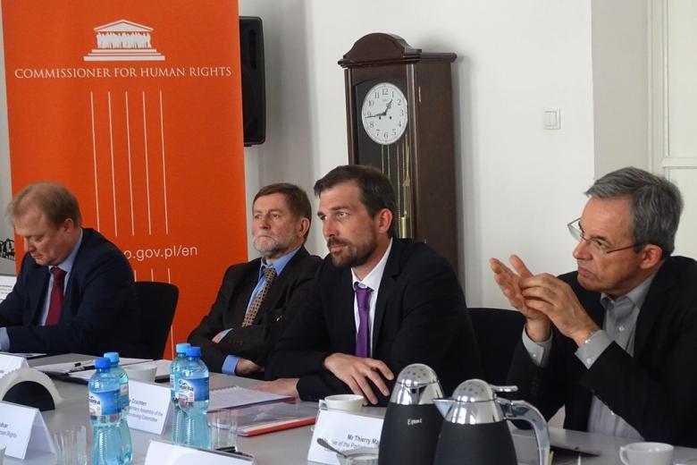zdjęcie: przy stole siedzi czterech mężczyzn w garniturach, w tle widać pomarańczowy baner