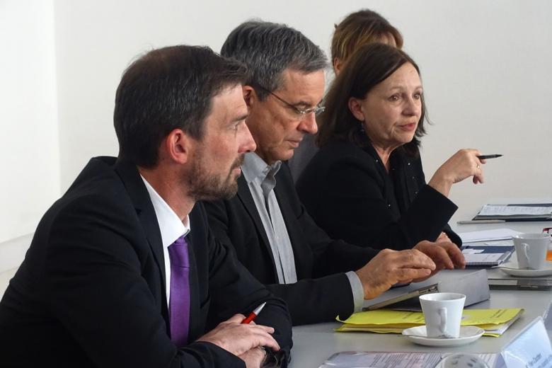 zdjęcie: dwaj mężczyźni i kobieta siedzą przy stole, kobieta zadaje pytanie