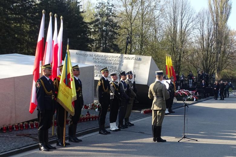 zdjęcie: po lewej stronie widać pomnik ofiat katastrofy smoleńskiej przed nim stoją żołnierze