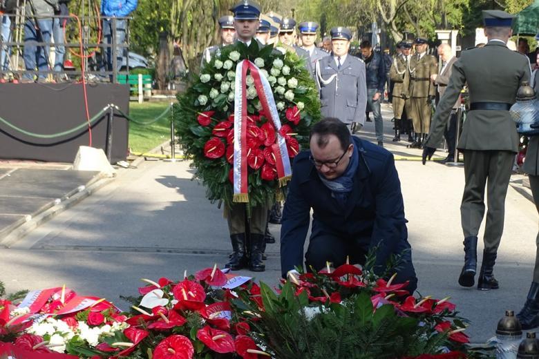 zdjęcie: mężczyzna składa wieniec, za nim stoją żołnierze