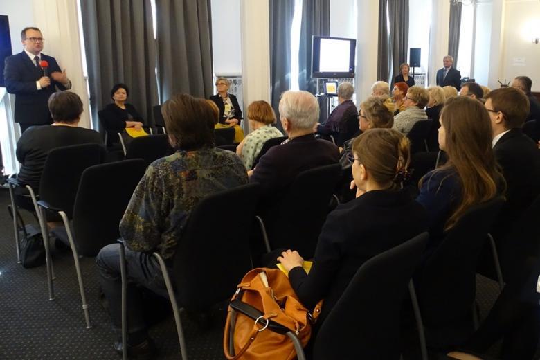 zdjęcie: kilkanaście osób siedzi na krzesłach przed nimi przemawia mężczyzna w garniturze