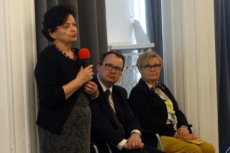 zdjęcie: kobieta swoi i mówi do mikrofonu, za nią siedzi mężczyzna i kobieta
