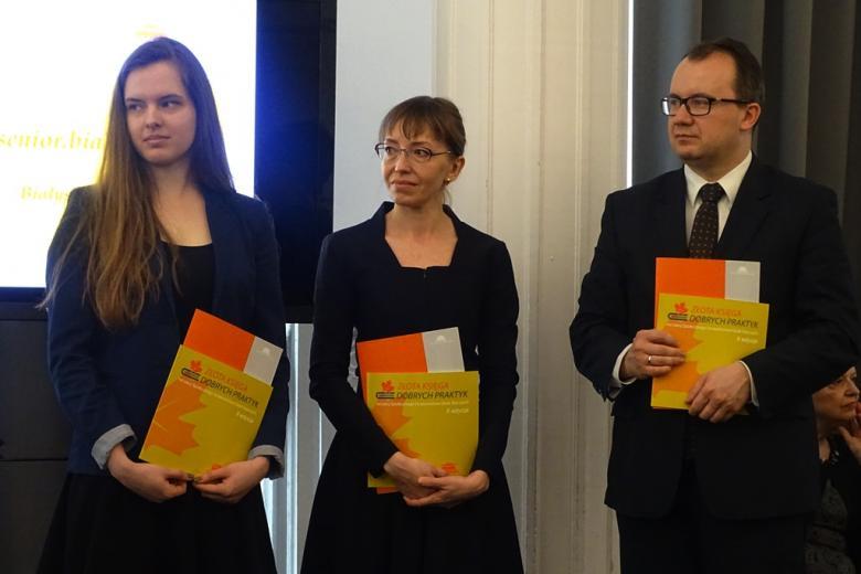 zdjęcie: dwie kobiety i mężczyzna stoj ai trzymają w rękach Złote księgi