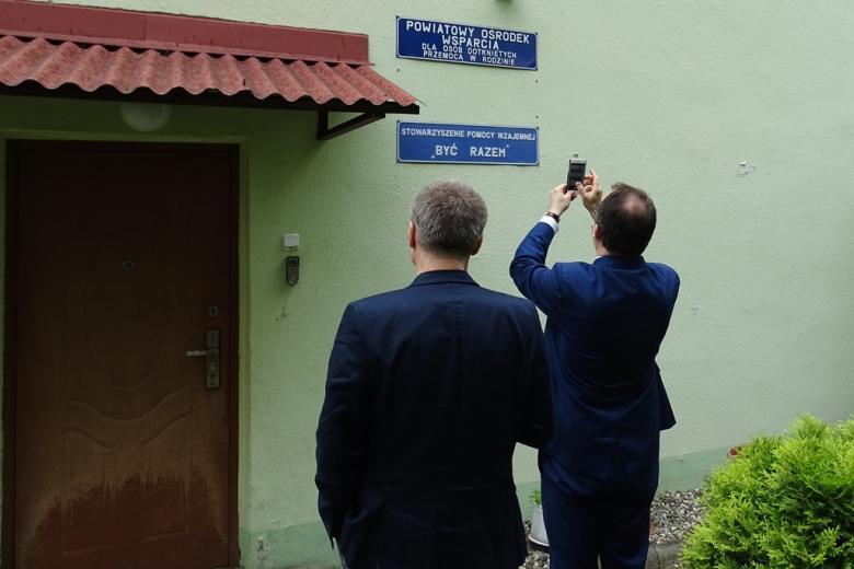 Mężczyźni fotografują tabliczkę przy wejściu