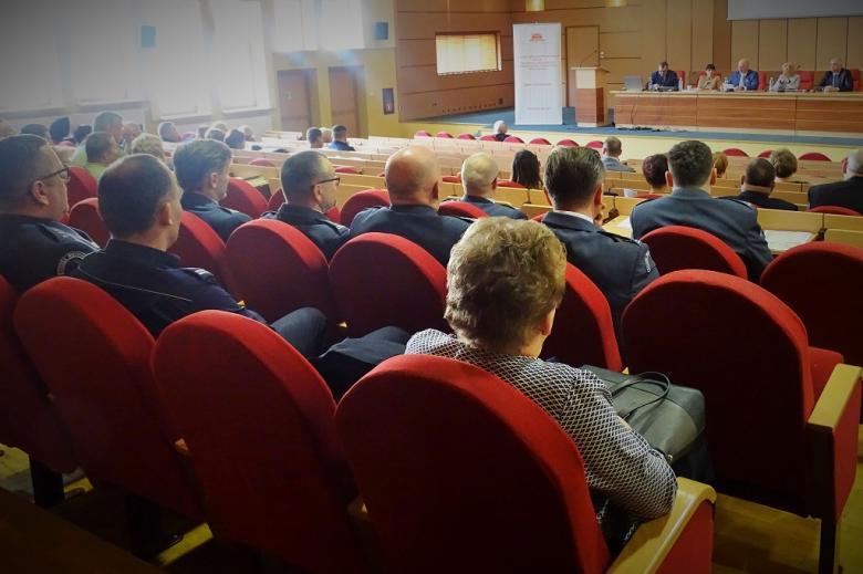 zdjęcie: na sali siedzi kilkadziesiąt osób przed nimi stół za którym siedzą dwie kobiety i trzech mężczyzn