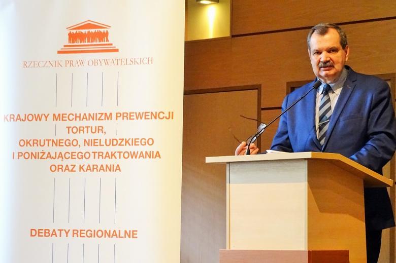 zdjęcie: meżczyzna w garniturze stoi przy mównicy