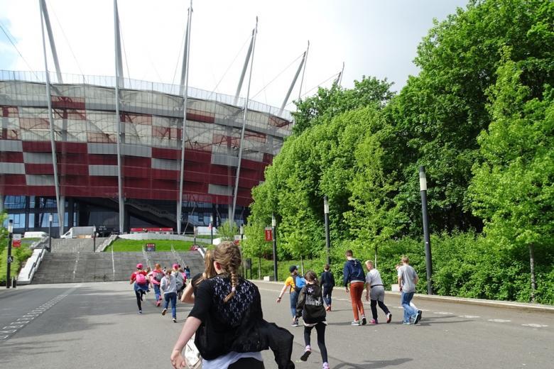 Dzieci biegną w stronę stadionu