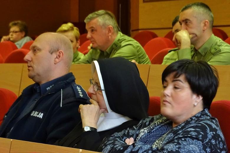 zdjęcie: w pierwszym rzędzie siedzi policjalnt i zakonnica, za nimi osoby w zielonych mundurach