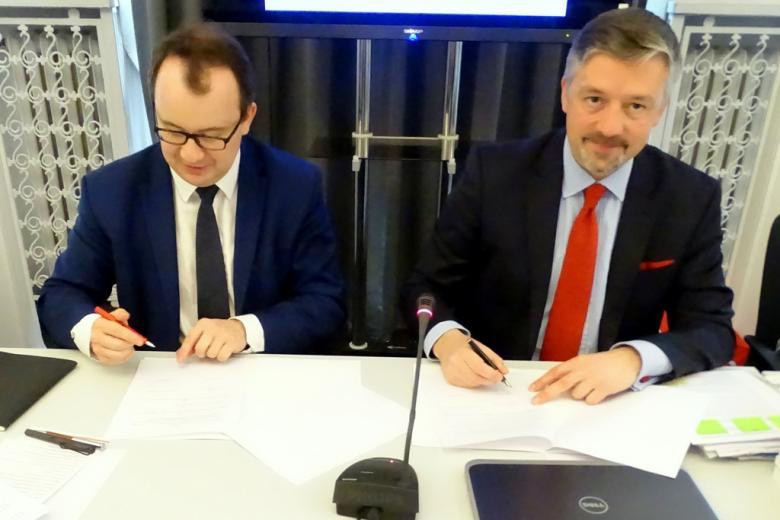zdjęcie: dwaj mężczyźni siedzą przy stole i podpisują dokumenty