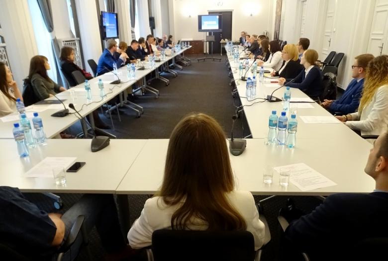 zdjęcie: przy stole ustawionym w kształcie  litery U siedzi kilkanaście osób