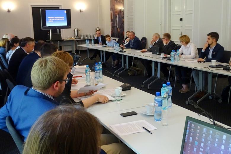 zdjęcie: przy stołach konferencyjnych siedzi kilkanascie osób